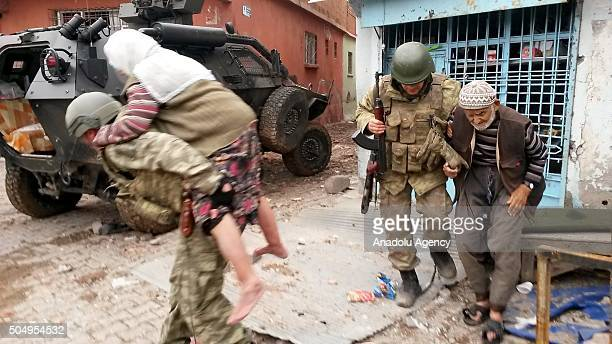Turkish soldier carries an old man on his back as he walks on the debris of the buildings in the Sur district of Diyarbakir Turkey on January 14 2016...