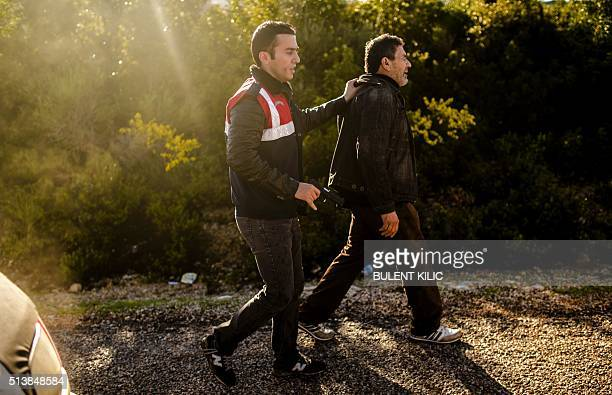 A Turkish soldier in plainclothes and holding a gun detains a suspected smuggler in Dikili western Turkey on March 5 2016 The number of migrants...