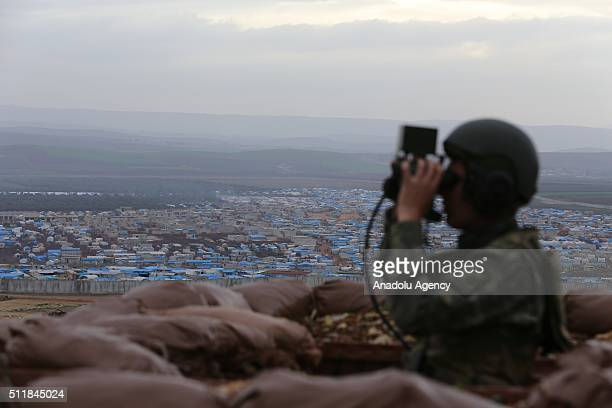 Turkish soldier looks at Atma tent camp through binoculars in the Reyhanli District of Hatay Turkey on February 23 2016 Yesilce and Bukulmez border...