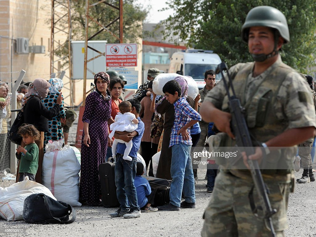 Turkish soldier stands guard as Syrian Kurdish refugees enter Turkey at the Yumurtalik crossing gate on September 24 2014 in Turkey As many as 138000...