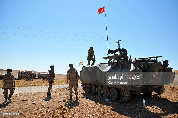 A Turkish soldier stands guard as Syrian refugees wait to cross into Turkey at the border September 22 2014 near the southeastern town of Suruc in...