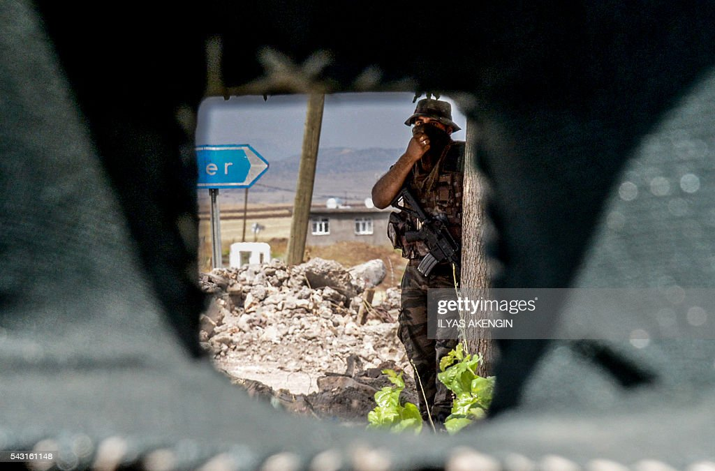 A Turkish soldier stands next a military check point as Members of Parliament of the pro-Kurdish Peoples' Democratic Party (HDP) and kurdish activists wait in a military check point as they want to enter Lice district in Diyarbakir on June 26, 2016. Militants from the outlawed Kurdistan Workers Party (PKK) on June 24, 2016 killed six Turkish soldiers in two separate attacks in the troubled southeast of the country, the army said. / AFP / ILYAS