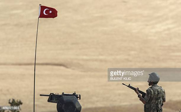 A Turkish soldier stands on a hill facing the Islamic State fighters' new position 10km west of the Syrian city of Ain alArab near the Syrian border...
