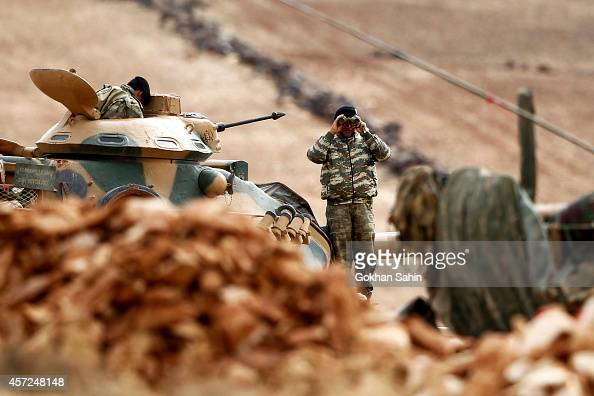 A Turkish soldier stands on a top of a tank as he watches the Syrian town of Kobani from near the Mursitpinar border crossing on the TurkishSyrian...