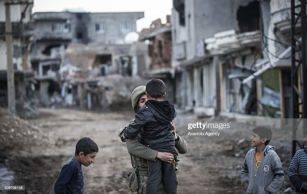 A Turkish soldier talks to children as Turkish security forces patrol around after counter-terror operation in Cizre, the southeastern Turkish town that has seen fighting rage between security forces and PKK terrorists finished, on February 12, 2016.