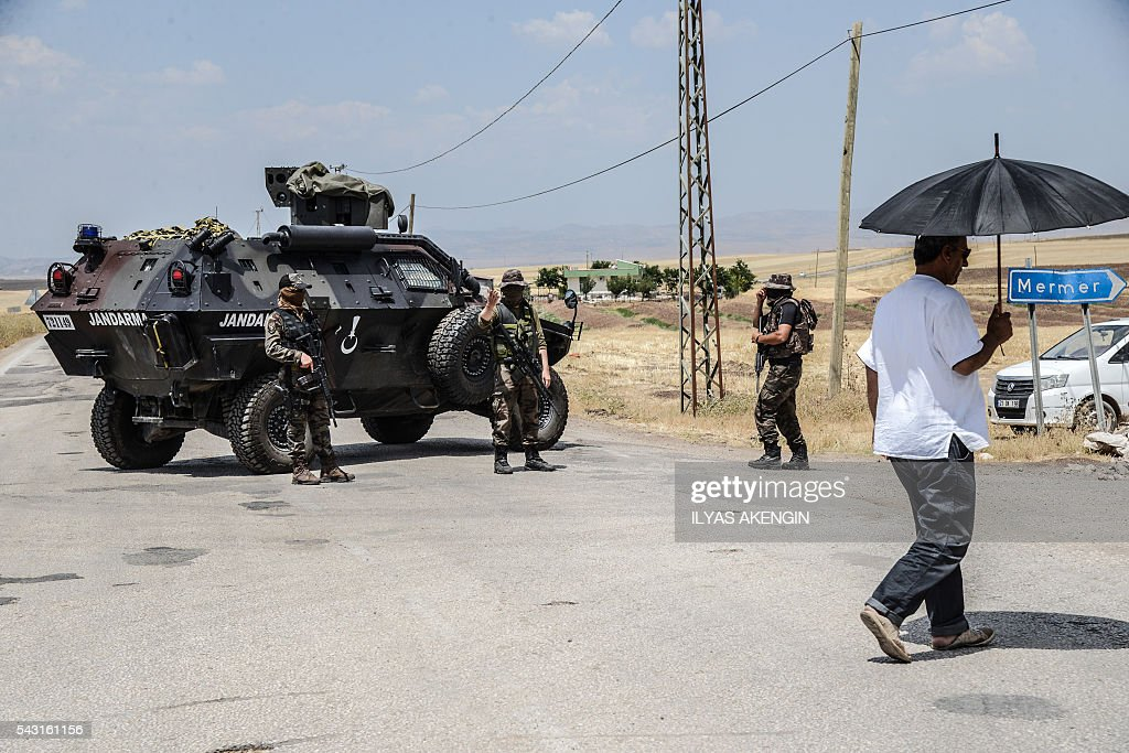 Turkish soldiers block the road at a military check point as Members of Parliament of the pro-Kurdish Peoples' Democratic Party (HDP) and kurdish activists wait in a military check point as they want to enter Lice district in Diyarbakir on June 26, 2016. Militants from the outlawed Kurdistan Workers Party (PKK) on June 24, 2016 killed six Turkish soldiers in two separate attacks in the troubled southeast of the country, the army said. / AFP / ILYAS
