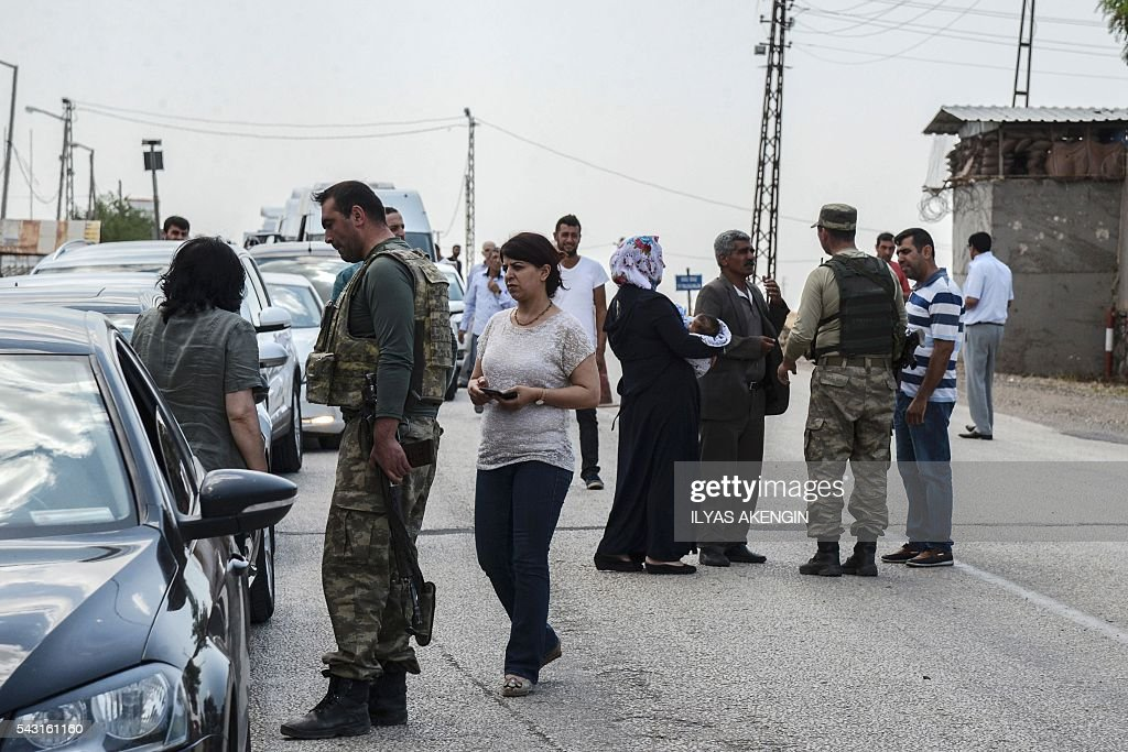 Turkish soldiers check cars at a military check point as Members of Parliament of the pro-Kurdish Peoples' Democratic Party (HDP) and kurdish activists wait in a military check point as they want to enter Lice district in Diyarbakir on June 26, 2016. Militants from the outlawed Kurdistan Workers Party (PKK) on June 24, 2016 killed six Turkish soldiers in two separate attacks in the troubled southeast of the country, the army said. / AFP / ILYAS
