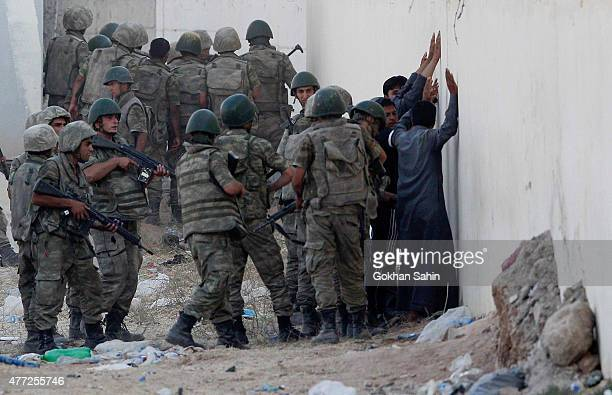 Turkish soldiers detain men came from Syria and supposed to be Islamic State fighters near the Akcakale crossing gate between Turkey and Syria at...