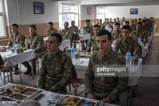 Turkish soldiers from the 1st Border Regiment Command are seen waiting to start lunch at a military outpost close to the Turkey/Syria border on March...