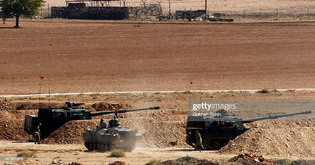 Turkish soldiers hold their positions with their artillery pieces in the outskirts of Suruc at the TurkeySyria border overlooking Kobani Syria...