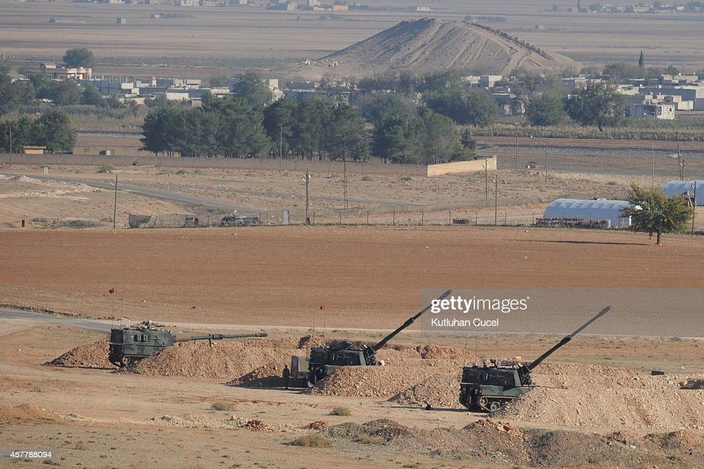 Turkish soldiers hold their positions with their artillery pieces in the outskirts of Suruc at the TurkeySyria border overlooking Kobani during...