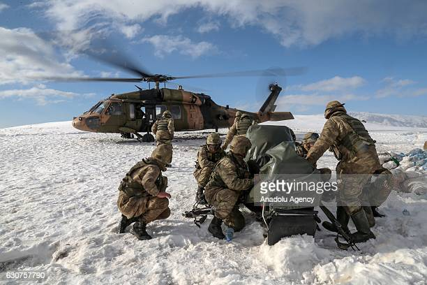 Turkish soldiers load a cargo into a military helicopter with its engine running in Hakkari Turkey on December 30 2016 Turkish Armed Forces...