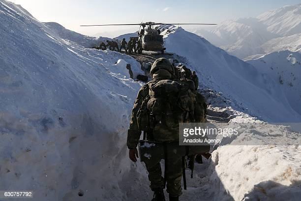 Turkish soldiers load cargoes into a military helicopter as others walk towards them in Hakkari Turkey on December 30 2016 Turkish Armed Forces...