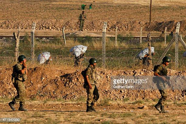 Turkish soldiers patrol as Syrian refugees walk to cross the Akcakale border gate in Sanliurfa province Turkey June 16 2015 Kurdish fighters took...