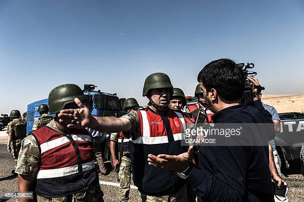 Turkish soldiers prevent a journalist from crossing the TurkeySyrian border post in Sanliurfa on September 4 prior to the arrival of the hearse...