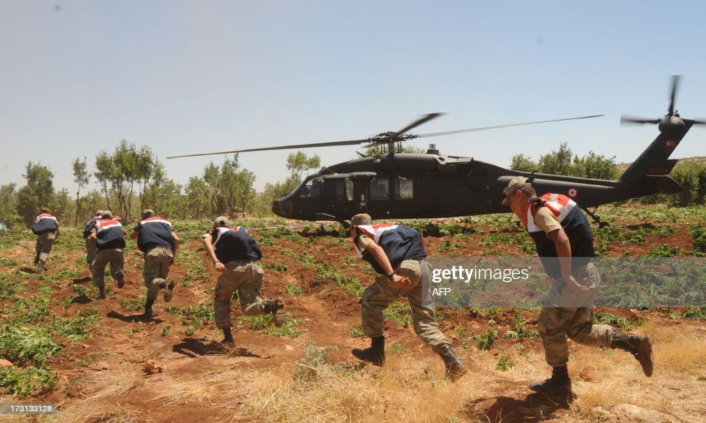 Turkish soldiers run through marijuana fields during an operation on July 8, 2013 in the Lice district of the southeastern city of Diyarbakir. AFP PHOTO /MEHMET ENGIN