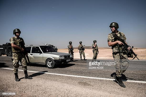 Turkish soldiers stand guar near the TurkeySyrian border post in Sanliurfa on September 4 following the crossing of the hearse carrying the body of...