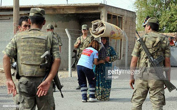 Turkish soldiers stand guard as a medic checks a Syrian Kurdish refugee woman as she enters Turkey at the Yumurtalik crossing gate on September 24...
