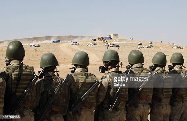 Turkish soldiers stand guard as protesters run away from tear gas during a proKurdish demonstration in solidarity with the people of Kobani near the...