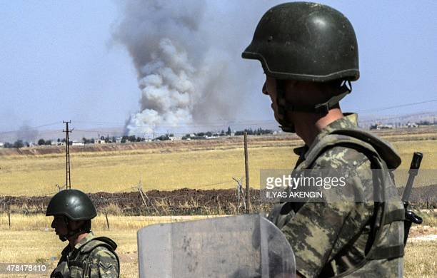 Turkish soldiers stand guard by the border with Syria on the way to Mursitpinar crossing gate in Suruc Sanliurfa province on June 25 2015 Turkey...