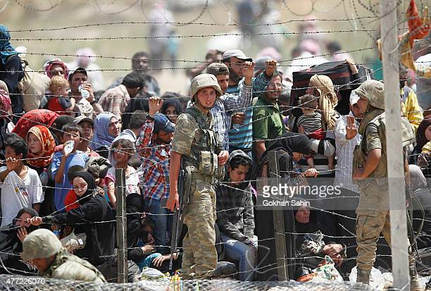 Turkish soldiers stand guarded as Syrian refugees wait on the Syrian side of the border to cross Akcakale on June 15 2015 in Sanliurfa province...