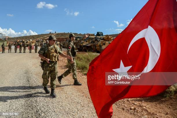 Turkish soldiers stand near armoured vehicles as a man waves a Turkish national flag during a demonstration in support of the Turkish army's Idlib...