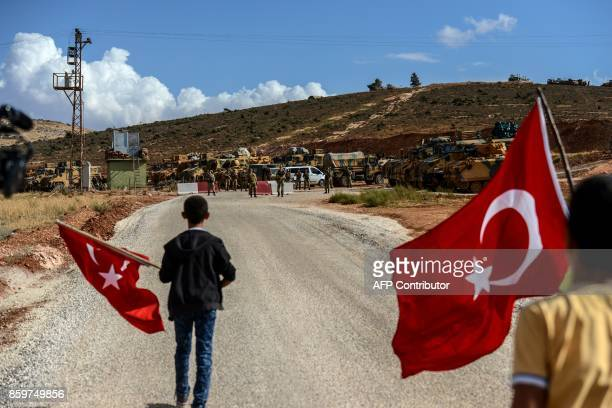 Turkish soldiers stand near armoured vehicles as two young boys waving Turkish national flags arrive during a demonstration in support of the Turkish...