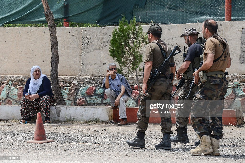 Turkish soldiers walk next to Members of Parliament of the pro-Kurdish Peoples' Democratic Party (HDP) and kurdish activists wait in a military check point as they want to enter Lice district in Diyarbakir on June 26, 2016. Militants from the outlawed Kurdistan Workers Party (PKK) on June 24, 2016 killed six Turkish soldiers in two separate attacks in the troubled southeast of the country, the army said. / AFP / ILYAS