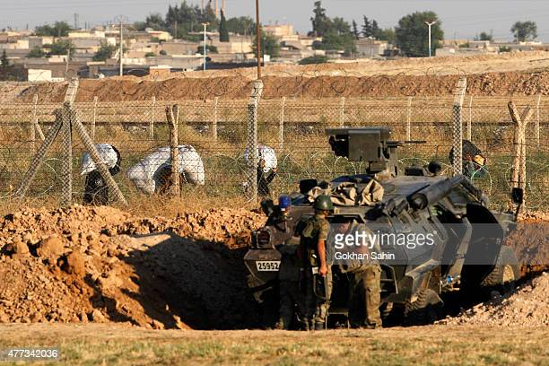 Turkish soldiers watch the Syrian refugees near the Akcakale border gate in Sanliurfa province Turkey June 16 2015 Kurdish fighters took full control...