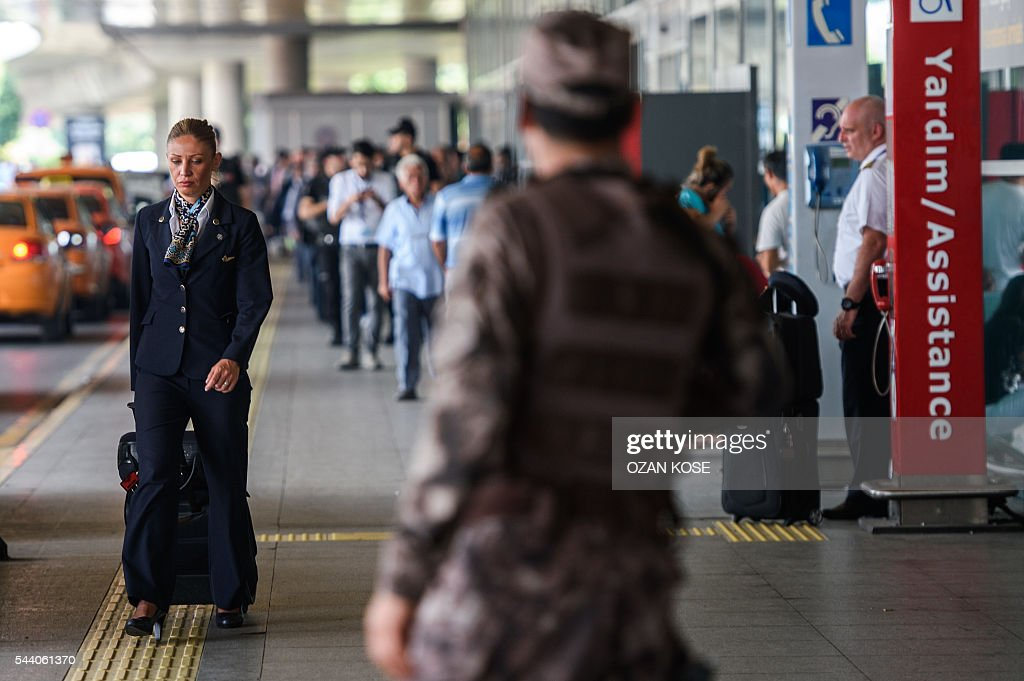 A Turkish special force police officer stands guard as a stewardess walks nearby the explosion site at the Ataturk airport International terminal on July 1, 2016 three days after a suicide bombing and gun attack targeted Istanbul's Ataturk airport, killing 44 people. The suicide attackers who launched the deadly Istanbul airport assault were planning to take dozens of passengers hostage, Turkish media reported on July 1, 2016, as CCTV of the bombers' faces emerged. Turkish officials have pointed blame at the Islamic State jihadist group for June 28 night's gun and bomb spree at Ataturk airport, which left 44 people dead including 19 foreigners. KOSE