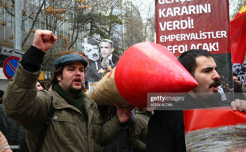 A Turkish student shouts slogans as others hold a mock missile during a protest against the Turkish government and NATO's deployment of patriot missiles near the Turkey-Syria border on December 21, 2012 in Ankara.