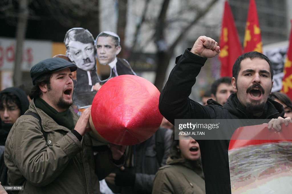 A Turkish student shouts slogans as others hold a mock missile during a protest against the Turkish government and NATO's deployment of patriot missiles near the Turkey-Syria border on December 21, 2012 in Ankara. AFP PHOTO/ADEM ALTAN