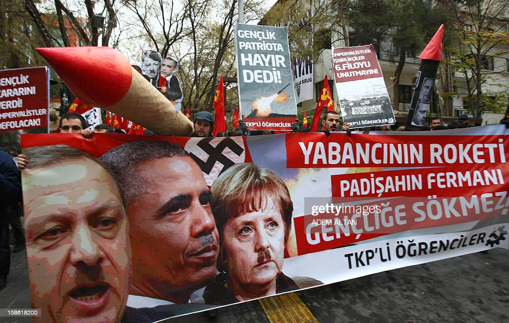 Turkish students hold a poster with photos of Turkish Prime Minister Recep Tayyip Erdogan (L), US President Barack Obama (C) and German Chancellor Angela Merkel looking like Adolf Hitler, during a protest against the Turkish government and NATO's deployment of patriot missiles near the Turkey-Syria border on December 21, 2012 in Ankara. The banner reads: ' The students will not obey before foreigner's rocket and sultan's decree! '