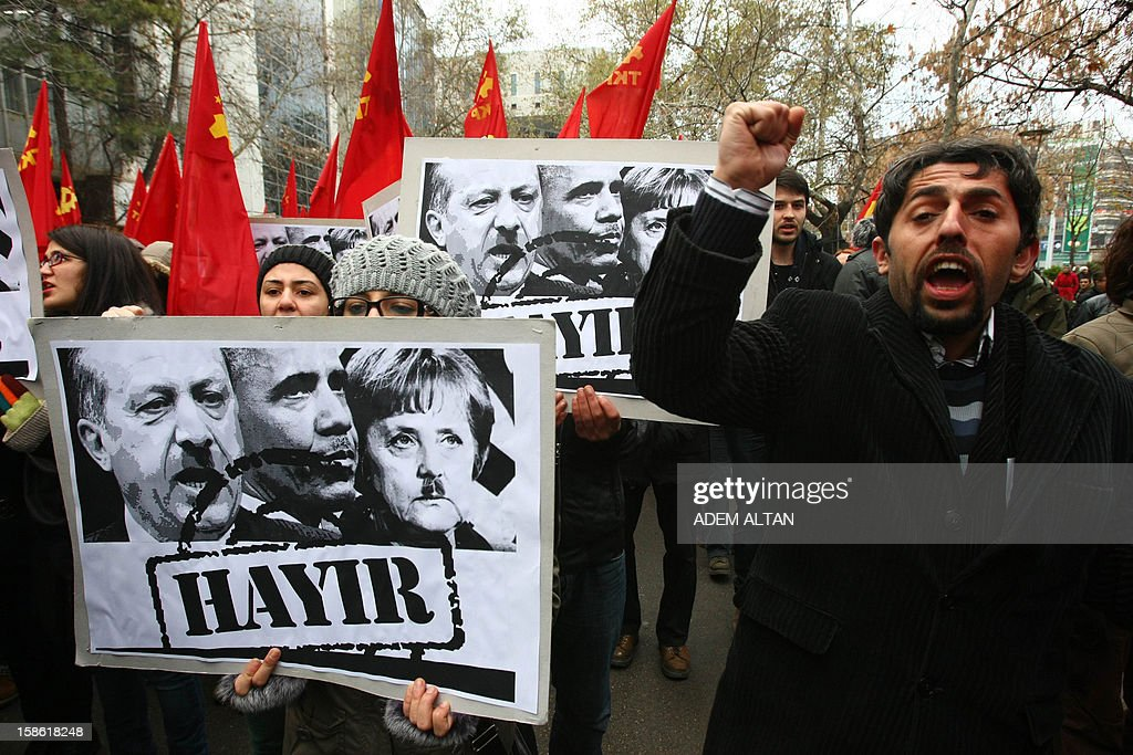 Turkish students hold a poster with photos of Turkish Prime Minister Recep Tayyip Erdogan (L), US President Barack Obama (C) and German Chancellor Angela Merkel looking like Adolf Hitler, during a protest against the Turkish government and NATO's deployment of patriot missiles near the Turkey-Syria border on December 21, 2012 in Ankara. The Turkish word on the banner reads: 'NO