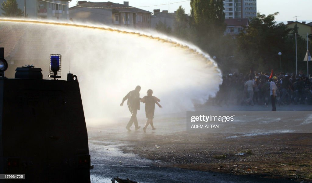 Turkish students spread from water cannon and tear gas fired by police during a protest on September 7, 2013 outside the Middle East Technical University (METU) in Ankara. From the day before, Turkish riot police confronted hundreds of university students in Ankara throwing stones and erecting barricades in protest against a project to build a road across part of their campus.