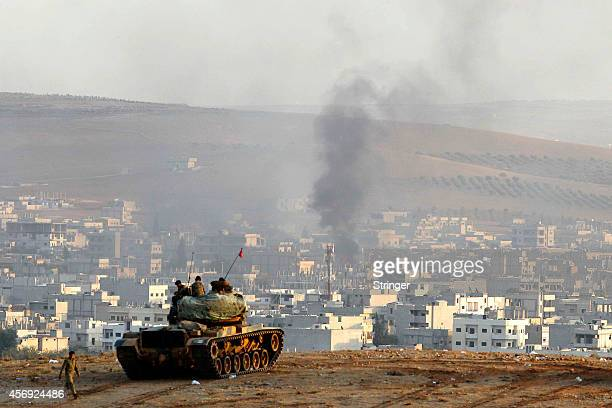 Turkish tanks hold their position on a hilltop on the outskirts of Suruc on the TurkeySyria border following an air strike in Kobani on October 9...