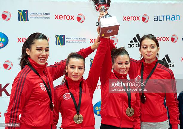 Turkish team members pose with their bronze medal during the podium ceremony for the women's team Kata event at the Karate world championships on...