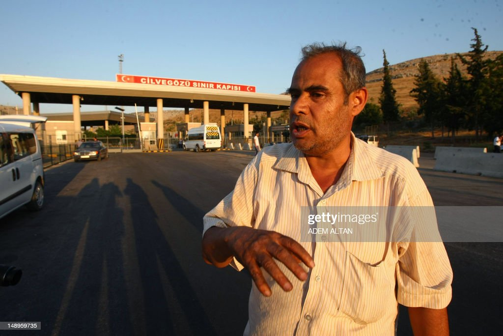 Turkish truck owner Huseyin Saz gestures after recovering his lorry and its driver and crossing into Turkey at Turkey's border post at Cilvegozu in the southern province of Hatay on July 20, 2012. Syrian rebel fighters took full control of the Bab al-Hawa border crossing in Syria, which lies opposite Turkey's Cilvegozu, in a battle with Syrian troops. Turkish trucks were claimed to have been burnt during fierce clashes between Syrian army troops and rebel fighters.