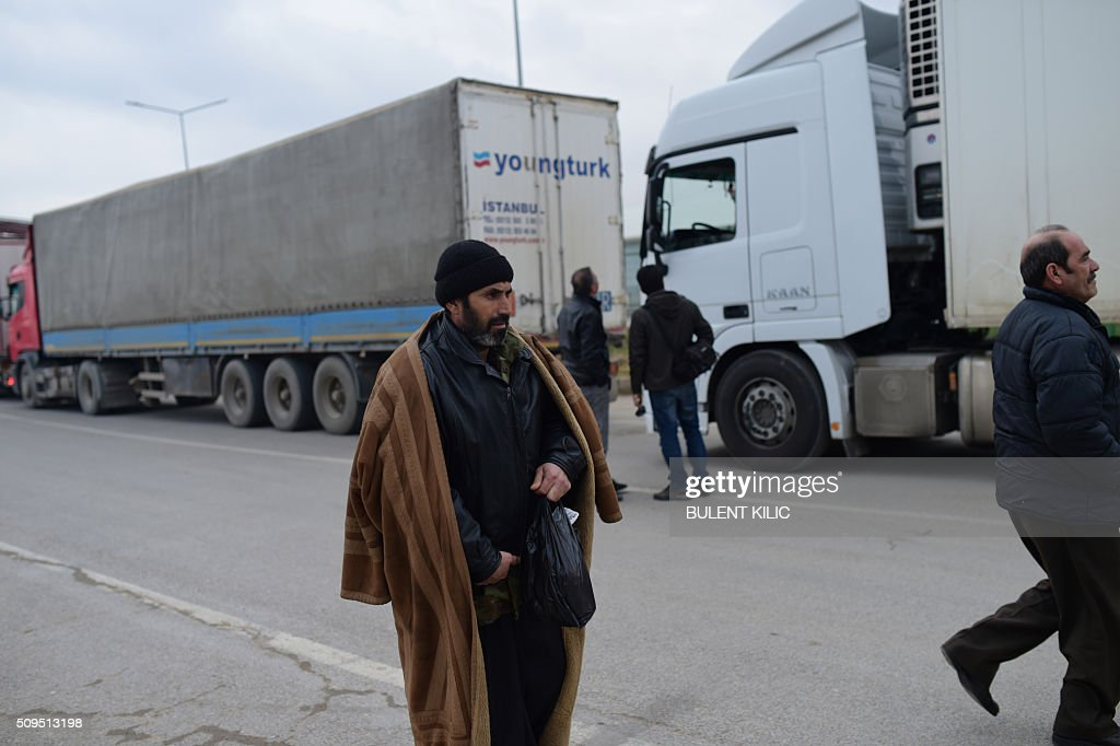Turkish trucks wait at the Oncupinar crossing gate, near the town of Kilis, in south-central Turkey, on February 11, 2016. Foreign ministers were gathering in Munich on February 11, with the West desperate to breathe new life into a Syrian peace process that has all but collapsed in the face of a Russian-backed onslaught against the opposition. / AFP / BULENT KILIC