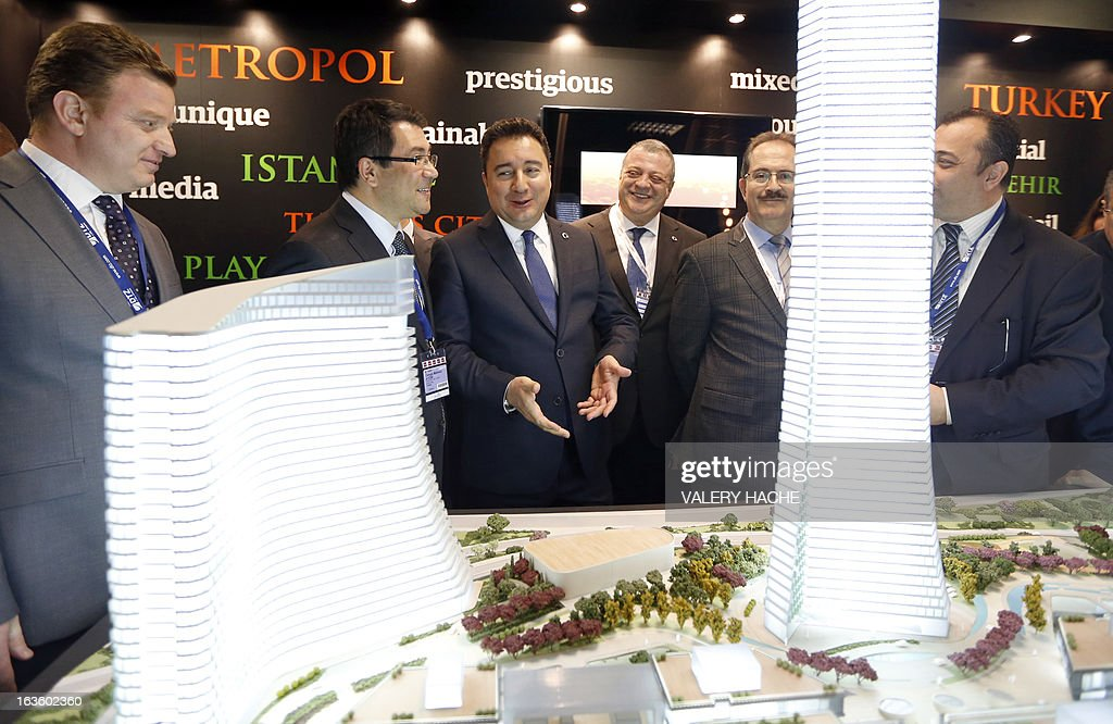 Turkish Vice Prime Minister Ali Babacan (C) looks at a scale model of the 'Metropol Istanbul Turkey' at the Palais des Festivals on March 13, 2013 in Cannes, southeastern France, during the MIPIM, an international real estate show for professionals. The event takes place until March 15.