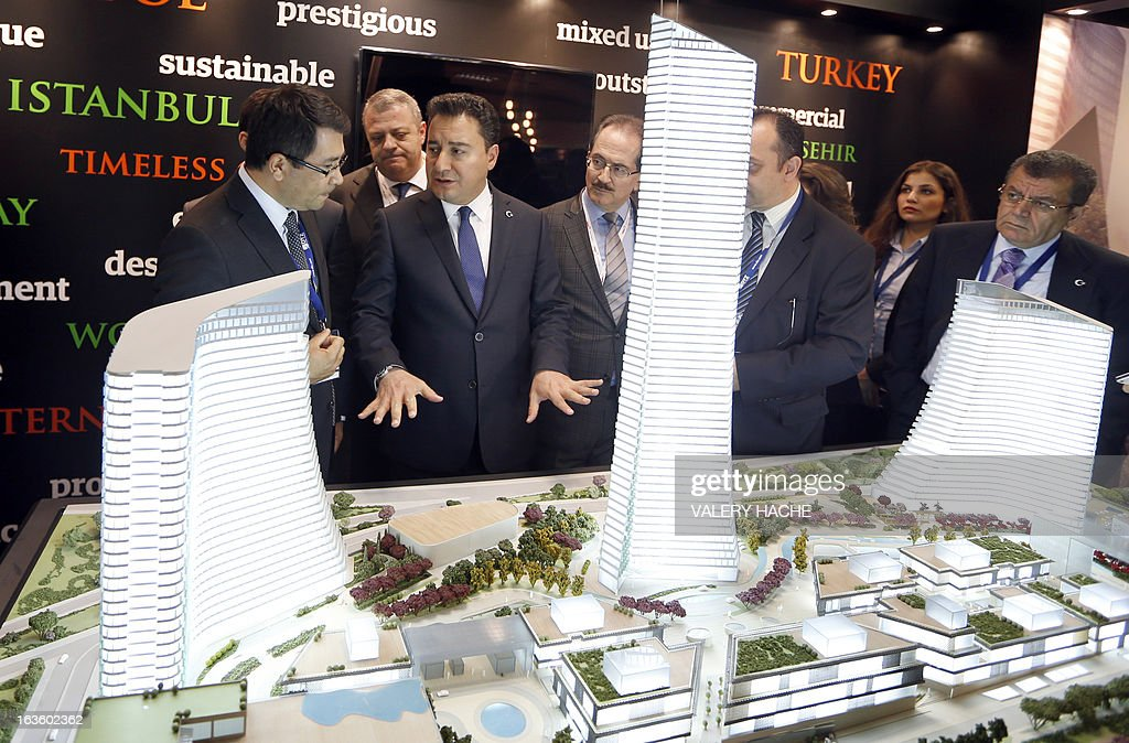 Turkish Vice Prime Minister Ali Babacan (2nd-L) looks at a scale model of the 'Metropol Istanbul Turkey' at the Palais des Festivals on March 13, 2013 in Cannes, southeastern France, during the MIPIM, an international real estate show for professionals. The event takes place until March 15.