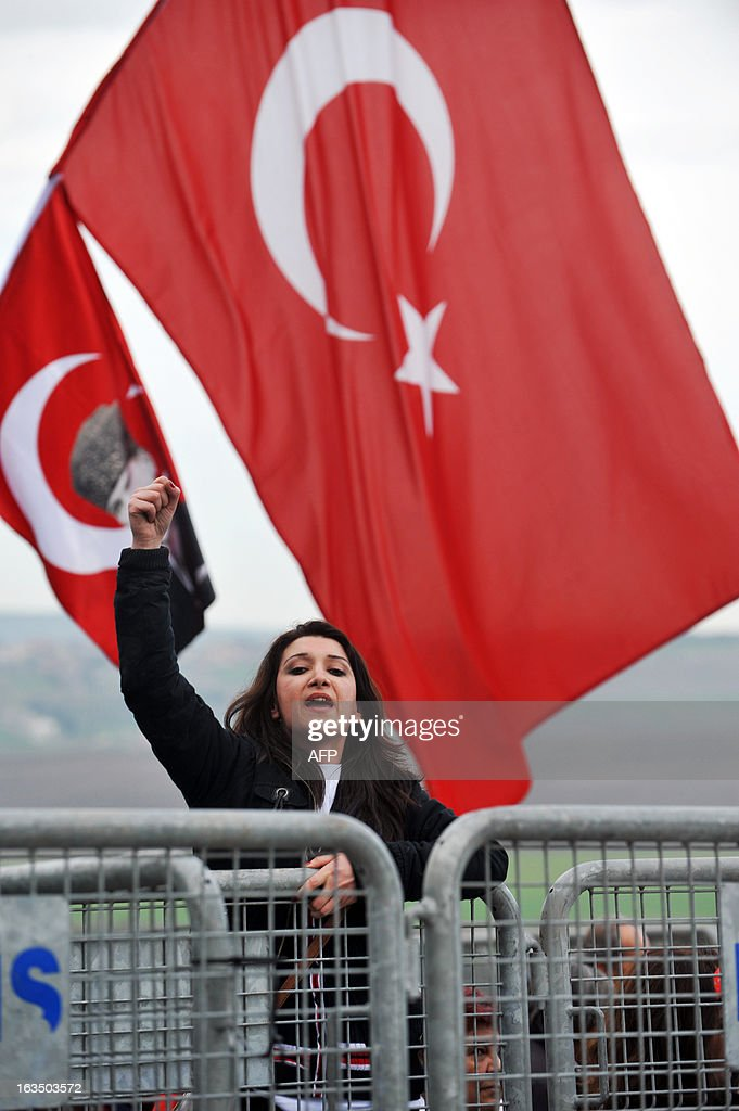 A Turkish woman chants slogans to protest behind gendarmerie barricades in Silivri near Istanbul on March 11, 2013 where prosecutors are scheduled to deliver their final arguments in the case against 275 people accused of plotting to overturn the Islamic-leaning government. A verdict in the four-year long case involving 275 defendants, including Turkey's former military chief Ilker Basbug and other army officers as well as lawyers, academics and journalists, is expected in the coming weeks. The defendants face dozens of charges, ranging from membership in an underground 'terrorist organisation' known as Ergenekon and instigating an armed uprising against Erdogan and his Justice and Development Party (AKP), which came to power in 2002.