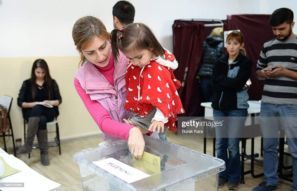 A Turkish woman holds her daughter as she casts her vote at a polling station during a general election on November 1, 2015, in Ankara, Turkey. Polls have opened in Turkey's second general election this year, with the ruling Justice and Development Party (AKP) hoping to win a majority, as the country searches for stability amongst serious security concerns.