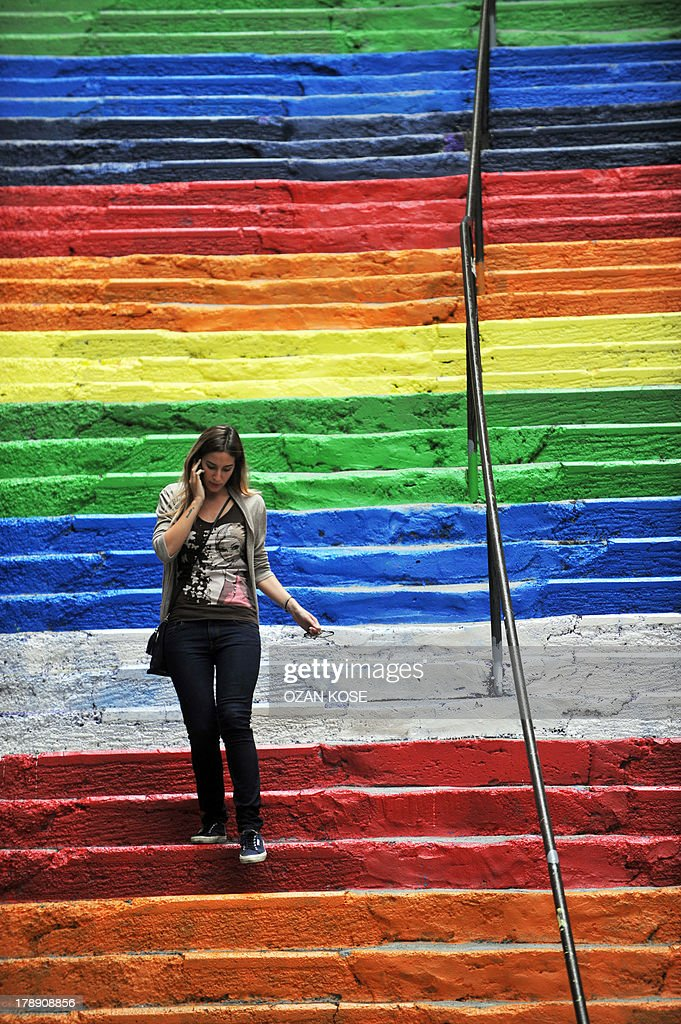 A Turkish woman takes pictures of rainbow-colored stairs on August 31, 2013 in Istanbul. Stairs in the Cihangir and Findikli neighborhoods, which attracted attention after being painted in rainbow colors by a local man on August 27, were all painted grey on the night of August. 29, and following comments on social media, the municipality of Beyoglu immediately painted them again in rainbow colors.