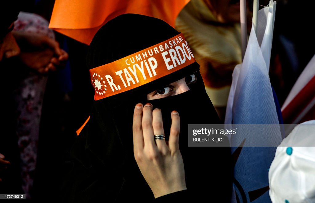 A Turkish woman wearing a niqab and a headband supporting the Turkish president attends a ruling Justice and Development Party party rally hosted by...