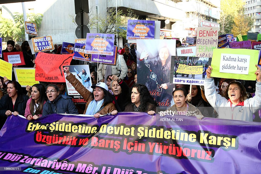 Turkish women, holding pictures of victims of domesctic violence, march on November 25, 2012 to condemn violence against women during a rally in Ankara during the International Day for the Elimination of Violence Against Women. Since 1999, the United Nations each year invites governments, international organizations and NGOs to organize activities designed to encourage the public to fight such violence. Banner reads: 'We walk against violence perpetrated by the state and men.' AFP PHOTO / ADEM ALTAN