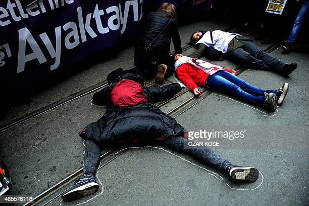 Turkish women lie on chalk outlines representing women victims during a rally in Istanbul to mark International Women's Day on March 8 2015 AFP PHOTO...