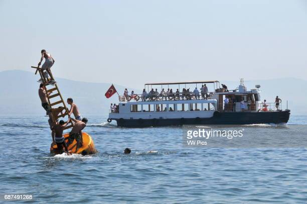 Turkish youths play on a buoy off the shore of K›nal›ada one of the Princes' islands while a little ferry carrying daytrippers sails by