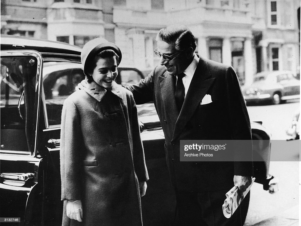 Turkish-born shipping billionaire Aristotle Onassis (1906 - 1975) pats his daughter, American-born shipping heiress Christina Onassis (1950 - 1988) on the shoulders as the pair get out of a car on their to eat lunch with Sir Winston Churchill, London, England, November 20, 1961.