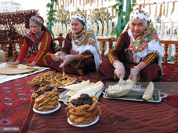 Turkmen women cut melons as they cook a sweet national dish during a Melon's Day holiday in Ashgabad on August 12 2012 A melon and watermelon were...